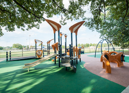 Inclusive PlayBooster® Vibe™ play structure with PebbleFlex safety surfacing.